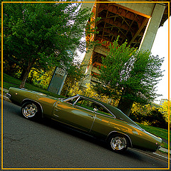 A green Dodge car on an alley